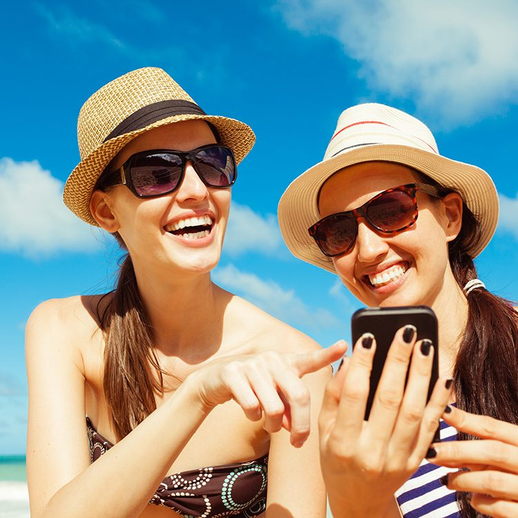 Pretty girls using smart phone on the beach. Summer holiday, tec
